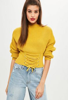 a8ed1265bc This sweater features in a mustard yellow hue with a corset lace up detail  on the