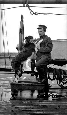 Ship's officer with pet dog, posed at ship's wheel, 1907-1928 - Samuel J Hood Studio