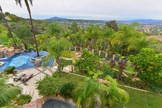 A bird's eye view of this La-Mesa backyard shows off the stunning pool and patio area, as well as a spa. Tropical trees and lush green plants are sprinkled throughout the landscaping.