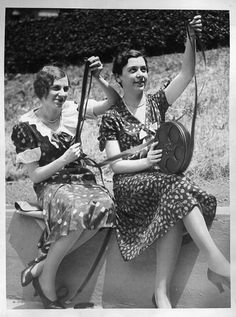 Two lovely 1930's women looking at film reels.