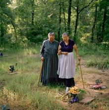 Sisters Maxine Wildcat Barnett (left) and Josephine Wildcat Bigler; two of the final surviving elderly speakers of Yuchi, visiting their grandmother's grave in a cemetery behind Pickett Chapel in Sapulpa, Oklahoma. According to the sisters, their grandmother had insisted that Yuchi be their native language.