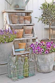 Vintage ladder, watering can and buckets, with lovely flowers. What a beautiful garden vignette.