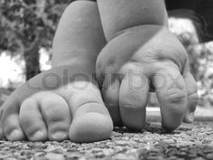 Stock image of '11 month old baby boy feet over rubber playpark floor. B&W Shot'