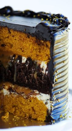Moist spicy pumpkin cake layered with dark chocolate cake, salted caramel, chocolate chip cream cheese filling, and topped with glossy, rich, and super-creamy dark chocolate frosting.