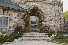 This amazing floral archway can be re-purposed to the head table for a beautiful floral garland. Florist: BLOOM | Photographer: E.C. Campbell Photography | Venue: Castle Farms - Knight's Courtyard