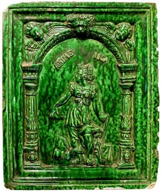 A 16th century German pottery stove tile in the manner of Hans Kraut of Villingen, moulded in relief with a figure of ARTIMEIKA (Artemesia) within a columned archway, surmounted by a lion mask and winged cherubs, covered in a mottled green translucent lead glaze, circa 1580, 11in x 9.25in.
