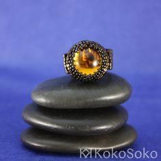 Diseño que combina un cabuchón redondo de cristal Swarovski en color ámbar con una montura marrón oscuro brillante de delicas de cristal japonés Miyuki.  Diámetro: 1.7cm  Recuerda que si no tenemos tu talla o prefieres otros colores, puedes encargarnos este anillo en la sección de A tu gusto.