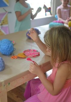 hand sewing a felt heart for her dream catcher, age six