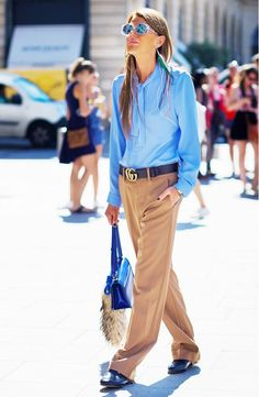 Anna Dello Russo wears a blue blouse, wide-leg belted trousers, Gucci slide loafers, a blue bag, and mirrored sunglasses