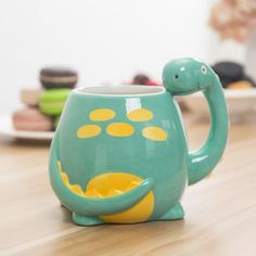 Adorable and functional, this cute Brontosaurus coffee mug will be loved by kids and adults alike! The hand painted and sculptured design features a long dinosaur neck as mug handle, and a colorful turquoise and yellow finish. Perfect for enjoying coffee or tea, or as a fun container for storing office supplies or other small items, this comic themed mug is a humorous gift to a friend or loved one or yourself! Product Features: Adorable brontosaurus dinosaur ceramic mug with yellow and… Cute Mugs, Funny Mugs, Dinosaur Mug, Cool Office Supplies, Clay Art Projects, Wine Display, Novelty Gifts, Ceramic Mugs, Ceramic Art