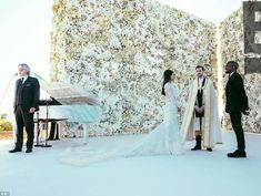 2014-05-24 Mr. & Mrs. Kanye West in a lovely Givenchy dress in front of a gorgeous wall of flowers. He gave her a tenor: Kanye West had Andrea Bocelli sing Kim Kardashian up the aisle.