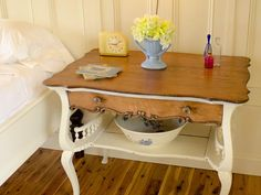 An antique table manufactured by E. H. Mason Office Furniture serves as a nightstand.