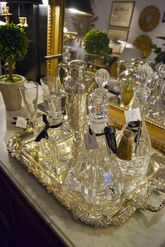 the black walls are set well with the gilt edged mirror, which reflects light onto the crystal decanters and silver tray