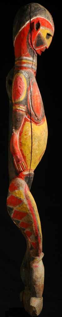 """Don't let the bright colors fool you. This is a very old Abelam female figure carved from a dense hardwood. Notice the  unusual posture not found on recent pieces—the figure's knock-knees jut forward, the butt is thrust back, there is an overly elongated torso and the head is looking down. Newer Abelam figures are more straightforward, more rigid. The nose and ears are pierced and the sex clearly defined as on all pre-1940 Abelam figurative sculptures. This one is 68"""" in height."""