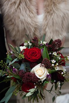 Winter Bridal bouquet at Farnham Castle. Bouquet made of Grand Prix, Black Baccara and Vendella Roses, Purple Tulips, Skimmia and Waxflower. Image taken by Philip Bedford