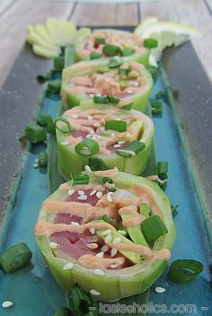 Cucumber wrapped sushi is low carb, paleo and versatile. Fill it with all your favorite ingredients and create a new roll! Our roll is filled with tuna, shrimp and avocado and topped with spicy mayo! www.tasteaholics.com