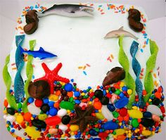 Under the Sea Cake ~ What a fun cake... M & Ms, jelly beans, and candy rocks as the bottom of the sea. Sour belts as sea weeds, sea creature shaped chocolates and toy sea creatures