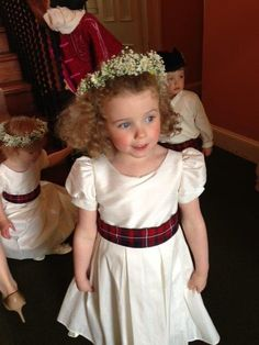 Scottish Wedding: flower girl's dress has family tartan sash. That's not a cute flower girl dress but adding the tartan sash is cute