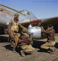 """""""Tuskegee"""" airman Edward Creston Gleed from Lawrence, Kansas, Class 42-K, with two unidentified crewmen adjusting an external seventy-five gallon drop tank on the wing of a P-51/D Mustang, """"Creamer's Dream"""" (generally flown by 1st.Lt.Charles White) 301st FS, 332nd Fighter Group air base in Ramitelli, Italy, March 1945. (Colorised by Sanna Dullaway)"""