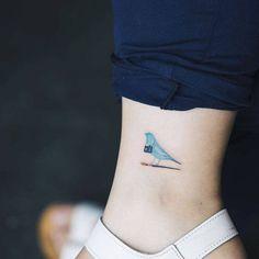 Tatuaje de estilo acuarela/surrealista de un pájaro azul con una...