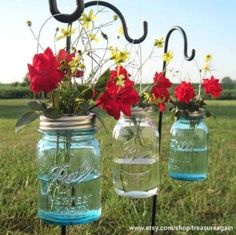 Hanging Mason (or Ball) jars with flower frog lids.