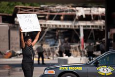 Protesters appeal to motorists for support while rallying on Aug. 11 in front of the QT gas station in Ferguson, Mo. that was looted and burned during rioting overnight that followed a candlelight vigil honoring 18-year-old Michael Brown, who was shot Aug. 9, by Ferguson police officers. Brown, who was killed in a confrontation with police in the St. Louis suburb, was shot Saturday and died following the confrontation with police. (Sid Hastings/Associated Press) #