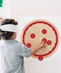 """Child playing """"Pin the Pepperoni on the Pizza"""""""