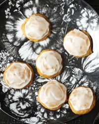These soft, lightly spiced cake-like cookies are studded with minced candied ginger and topped with a buttery sugar glaze.