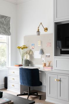 A brass swing arm sconce fixed over a pin board lights a light gray built-in desk painted in Benjamin Moore Graytint. Office Built Ins, Built In Desk, Blue Home Offices, Deeper Shade Of Blue, Ceiling Trim, Entry Wall, Grey Desk, Velvet Cushions, Shower Floor