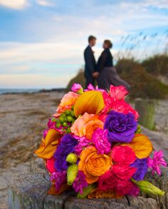 stunning colorful wedding bouquet is the focal point on this beach wedding photo on Folly Beach