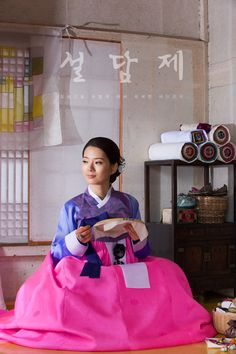 Woman in Hanbok, doing the traditional embroidery.