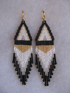 """These pretty chandeliers are handmade with both 6mm black & 12mm black bugle beads, golden, black, white luster, white opaque, transparent white crystal delica seed beads, with 3mm black fire polished crystals. They measure 4"""" long including the leverback earwires, & about 1"""" wide."""