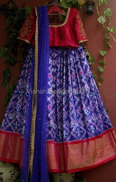 Blue ikkat lehenga paired with reddish pink hand embroidered blouse and blue net dupatta. Size can be customised. Lehenga Blouse Designs Back, Half Saree Designs, Salwar Designs, Choli Designs, Lehenga Designs, Mehndi Designs, Party Wear Indian Dresses, Dress Indian Style, Indian Fashion Dresses