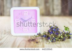 Bright pink  wall clock on a wooden table.  pastel tones.Selective focus - stock photo