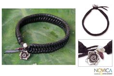 <li>Silver rose blossoms on a nest of woven leather make up the exclusive design of this bracelet<li>Khun Boom highlights her handmade jewelry with a shimmering freshwater pearl and garnet<li>Bracelet features accents made of .925 rating silver