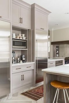 Gorgeous white and gray kitchen features two recessed stainless steel refrigerators flanking gray shaker cabinets fitted with aged brass pulls and folding doors open to reveal a a coffee station featuring shelves holding a microwave.