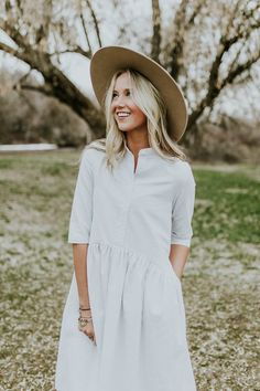 This white dress is taken to the next level with thin black stitched stripes and hidden seam pockets. A functional button up front is paired with an elegantly rounded gathered babydoll waist, resulting in comfort + style for days. With so many refined + timeless details, this dress is sure to become...