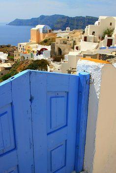 Blue wooden gate and sea view. Oia, Santorini island, Cyclades, Greece