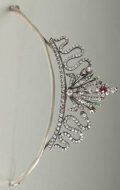 Um diamante, rubi, tiara esmeralda conversível centrando um broche destacável motivo floral, definido com um rubi e esmeraldas em forma de oval, acentuado por antigos diamantes Europeu de corte criados em ouro com tampo de prata, tiara com serpentes set-diamante ao longo de um arco de rosa diamantes -cut, com um ouro catorze quilates e cabeça peça de metal branco;  Estima o peso do diamante no total: 6,25 quilates.  por ilene