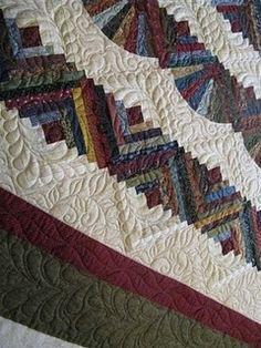 log cabin - beautiful quilting, soothing colors, and look at the Dresden Plate halves in there. Beautiful!