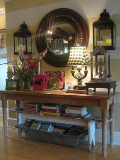 entry table | love the large mirror, books, flowers, lighting and large table.