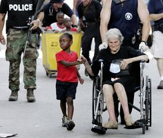 Hurricane Katrina Evacuation - 2005 - Tanisha Belvin, 5, holds the hand of fellow Hurricane Katrina victim Nita LaGarde, 89, as they are evacuated from the Convention Center in New Orleans. Hundreds of people waited several days to be evacuated.