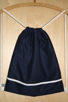 Turnbeutel aus dunkelblauem Baumwollstoff mit weißem Kunstleder-Streifen und gepunktetem Innenfutter.
