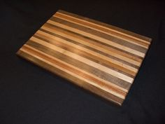 """Here is another rather large cutting board, this one weighs about 13lbs! This is approximately 13"""" x 19"""" x 1-3/4"""" and is made of Walnut, Maple, and Bloodwood. This color scheme is actually one of my favorites out of the 26 (lol! this is the 26th board) boards that I have made so far. As usual, I applied the same finish process as I do on all of my cutting boards… General Finishes/Mineral Spirits with many coats and light sanding until I am happy! :)"""