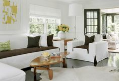 This fantastic Hamptons living room features a bright white sofa and chairs with chocolate brown two toned seat cushions. To make sure guests don't think the chocolate on the seat is an after thought, each piece of upholstered furniture has corner kick pleats revealing a bit more of that rich chocolate brown. Then to tie things together even more...a few brown throw pillows with white piping (or flange) are added into the mix