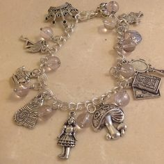 Alice in wonderland charm bracelet Disneyland .) Alice in wonderland charm bracelet. Not real. Fashion jewlery. Brand new in bag it came in. Bought on Etsy for a party. Has 11 charms(Disneyland) etsy Jewelry Bracelets