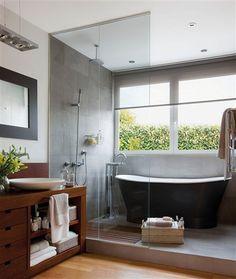 Baño con ducha y bañera exenta separados del resto del baño por mámpara de cristal