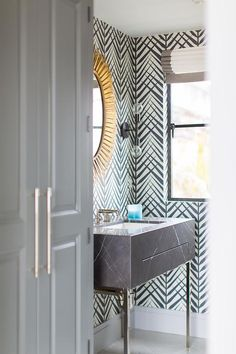 A gold oval sunburst mirror is hung from a wall clad in ivory and black palm wallpaper and is positioned over a black marble sink vanity finished with a polished nickel faucet.