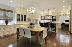 Spacious white kitchen with eat-in peninsula in addition to dining table situated in the center of the kitchen. White cabinetry offset with dark wood flooring
