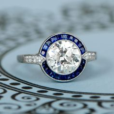 Deep blue sapphires surrounding an old European cut diamond, and set within a gorgeous handcrafted platinum mounting.
